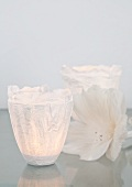 Artistic tealight holders made from tissue paper, paste and transparent film next to delicate white flower