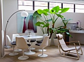 White shell chairs at round table and arc lamp in corner of loft apartment