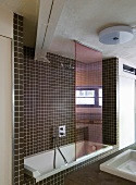 Bathtub in niche with brown mosaic wall tiles