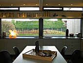 Dining area in front of modern kitchen counter below large windows with view of garden