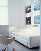 Weisses Sofa vor Photograpien hinter Glas und Bauhausstuhl