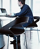 Man seated on designer chair working on laptop