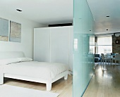 Glass partition separating sleeping area in open-plan living space