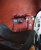 Modernes Sofa mit grauem Samtbezug vor Musikinstrumenten an rotbrauner Wand