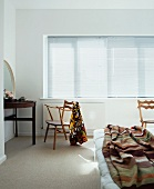 Bedroom with 50s wooden chair at dressing table in front of closed window blinds