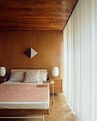 Double bed in wood-panelled, 50s-style bedroom
