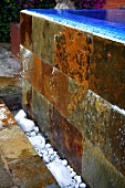Stone tiles on exterior of negative edge pool