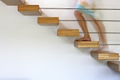 Blurred legs of bare-footed woman on floating staircase construction with wooden treads projecting from wall behind delicate baluster rods