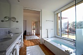 Bright bathroom with floor-to-ceiling window, sliding door and terracotta tiles