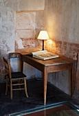 Tischlampe auf Holztisch vor Wand mit verblasster Schablonenmalerei