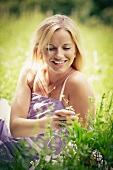 Young, blonde woman sitting in meadow