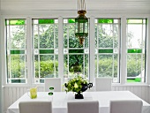 Table with white cloth and white chairs in dining room with Art Deco window
