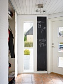 Cloakroom wardrobe with sliding curtain doors and blackboard in hall