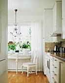 White, antique console table and chair below window lend a romantic, vintage air to a modern kitchen