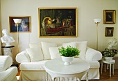 White sofa with valance and vintage coffee table between antique busts and against wall with paintings from various periods