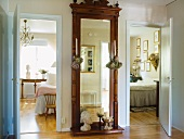 Antique, full-length mirror with ornate frame in hallway between bedroom and guest room