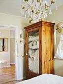 Glass-fronted wooden wardrobe in bedroom