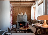 Open fireplace in corner of rustic room with furniture in a mix of styles