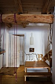Swing suspended from wooden beam below ceiling and wooden staircase with landing