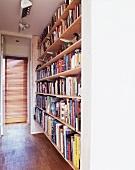 Raumhohes Bücherregal neben offener Tür mit Blick auf Glastür und Jalousie