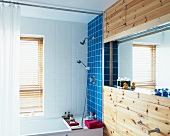 Simple bathroom with coloured tiles above bathtub and mirror in niche of wood-clad wall