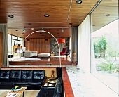 Fifties-style, open-plan living space with sofas in sunken seating area