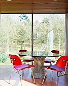 Wooden chairs stained red at glass table in front of floor-to-ceiling terrace doors with a view