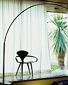 Fifties-style wooden chair in front of half-closed curtain at window and view of yucca