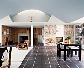 Modern, open-plan living space with dining area and fifties furniture on dark tiled floor