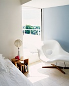 White chaise longue in front of terrace door in bedroom