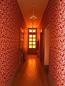 Narrow hall with ornate red and white patterned wallpaper