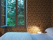 Bedroom with ornate gold and white patterned wallpaper and open window