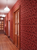 Hall with ornate wallpaper in various shades of red and artificial lighting
