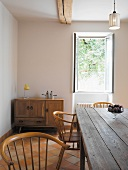 Rustic table and wooden chairs in front of open window in dining room