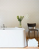 Chair next to free-standing bathtub in front of white tiled wall