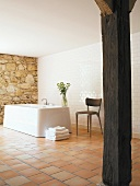 Rustic wooden column in modernised bathroom with free-standing bathtub