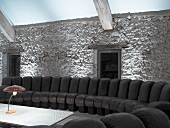Curved black leather couch in front of illuminated stone wall