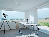 Desk in front of panoramic window in white-painted wooden house