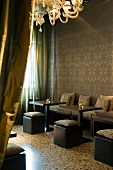 View past mustard-coloured silk curtain into vintage Venetian-style hotel lobby with cushions on black cubic stools and terrazzo flooring