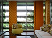 70s-style, small, green upholstered armchair with patterned cushion in front of louver blinds and orange sliding curtains
