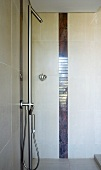 Shower with sunken base, designer fittings and vertical tiling trim in dark marble