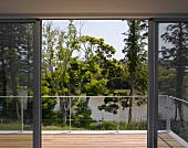 Open sliding doors to wooden terrace with intricate metal balustrade and view of trees and lake