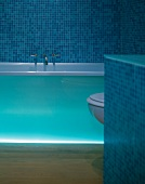 Bathtub with indirect lighting in bathroom with blue mosaic tiles
