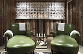 Green leather couches in front of wooden shelving with towels