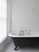 Bathtub in front of marble wall