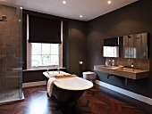 Bathroom with free-standing bathtub and brown walls