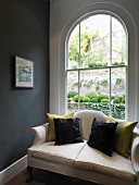 Sofa with cushions in front of arched window