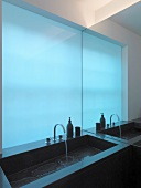 Designer sink in front of blue glass wall