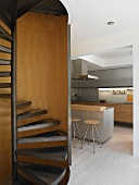 Spiral staircase with kitchen counter and bar stools in background