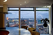 Round kitchen counter with integrated hob in front of large windows with a view of London